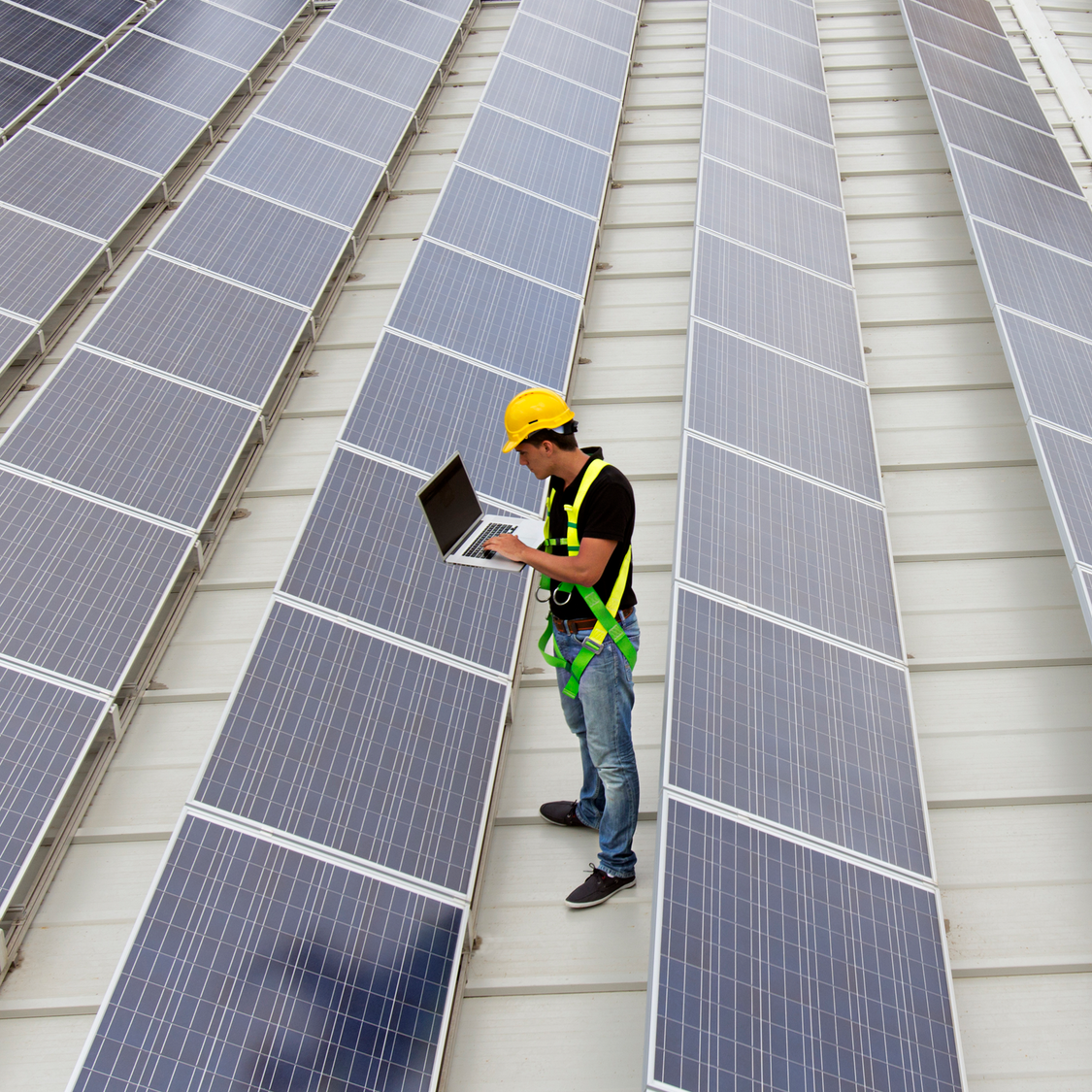 Technician with laptop standing around mounted solar panels, testing and calibrating the system