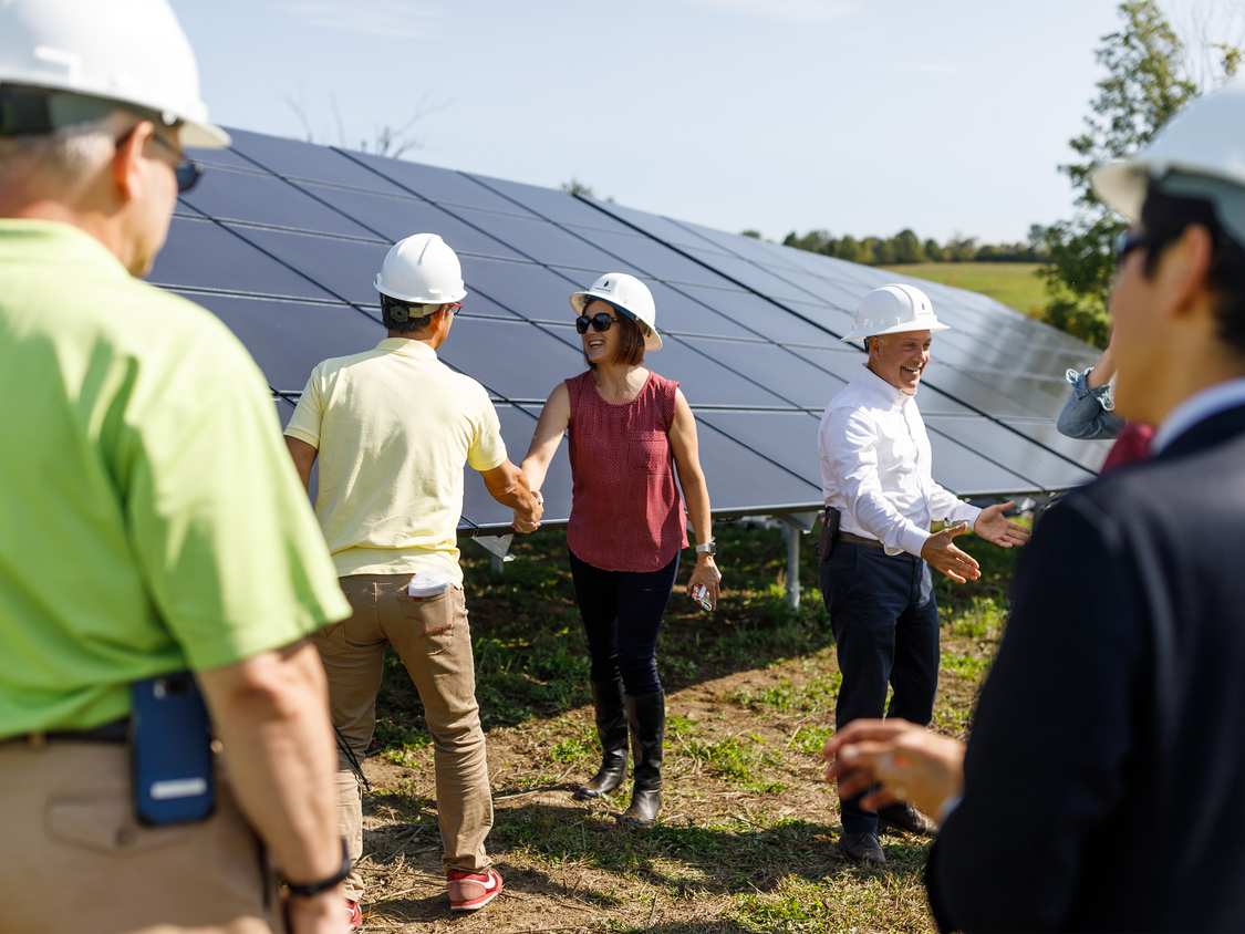 Woman and man shaking hands in front of solar panels and a crowd of partners in a solar energy investment