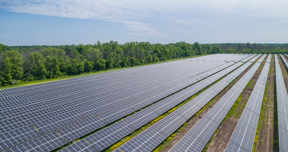 Technicians reviewing large-scale solar energy installa